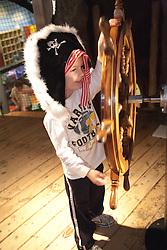 United States, Washington, Bellevue, KidsQuest Children's Museum, boy in prate hat turning ship's wheel