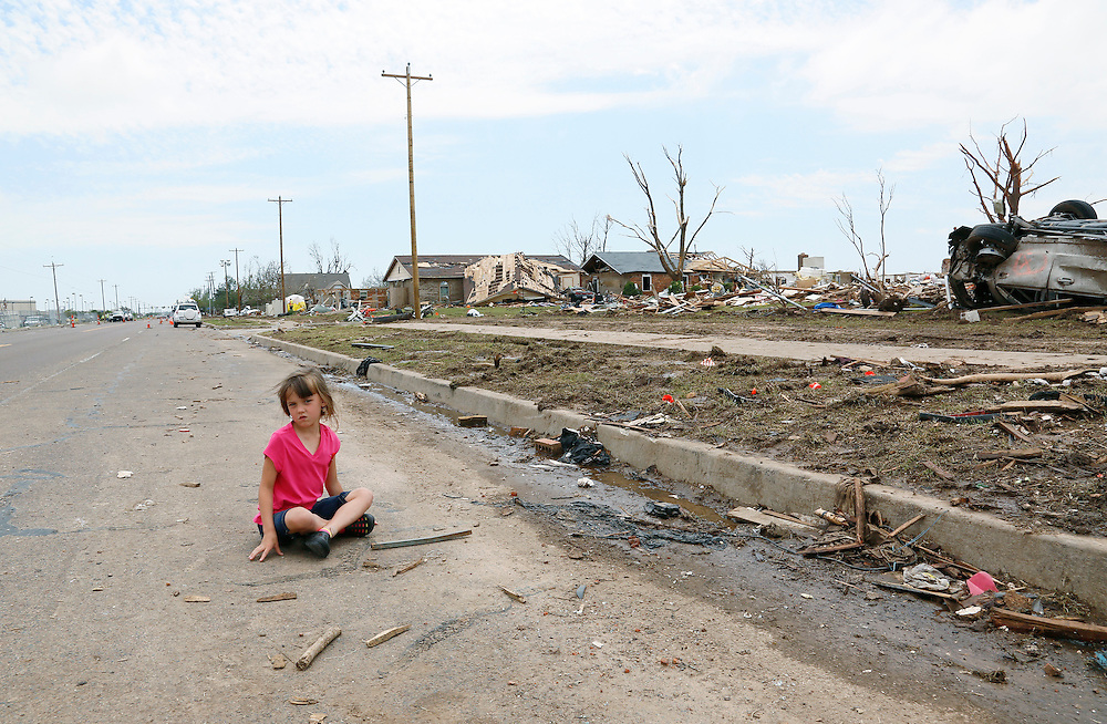 Abigail Stephan, 6, sits in the road waiting for her mother to show her their tornado-destroyed home on 6th Avenue for the first time since the storm  in Moore, Oklahoma May 23, 2013. The tornado was the strongest in the United States in nearly two years and cut a path of destruction 17 miles long and 1.3 miles wide. REUTERS/Rick Wilking (UNITED STATES)