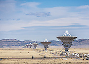 """The Karl G. Jansky Very Large Array (VLA) is one of the world's premier astronomical radio observatories. Visit the VLA on the Plains of San Agustin fifty miles west of Socorro, between the towns of Magdalena and Datil, in New Mexico, USA. US Route 60 passes through the scientific complex, which welcomes visitors. The VLA is a set of 27 movable radio antennas on tracks in a Y-shape. Each antenna is 25 meters (82 feet) in diameter. The data from the antennas is combined electronically to give the resolution of an antenna 36km (22 miles) across, with the sensitivity of a dish 130 meters (422 feet) in diameter. After being built 1973-1980, the VLA's electronics and software were significantly upgraded from 2001-2012 by at least an order of magnitude in both sensitivity and radio-frequency coverage. The VLA is a component of the National Radio Astronomy Observatory (NRAO). Astronomers using the VLA have made key observations of black holes and protoplanetary disks around young stars, discovered magnetic filaments and traced complex gas motions at the Milky Way's center, probed the Universe's cosmological parameters, and provided new knowledge about interstellar radio emission. The VLA was prominently featured in the 1997 film """"Contact,"""" a classic science fiction drama film adapted from the Carl Sagan novel, with Jodie Foster portraying the film's protagonist, Dr. Eleanor """"Ellie"""" Arroway, a SETI scientist who finds strong evidence of extraterrestrial life."""