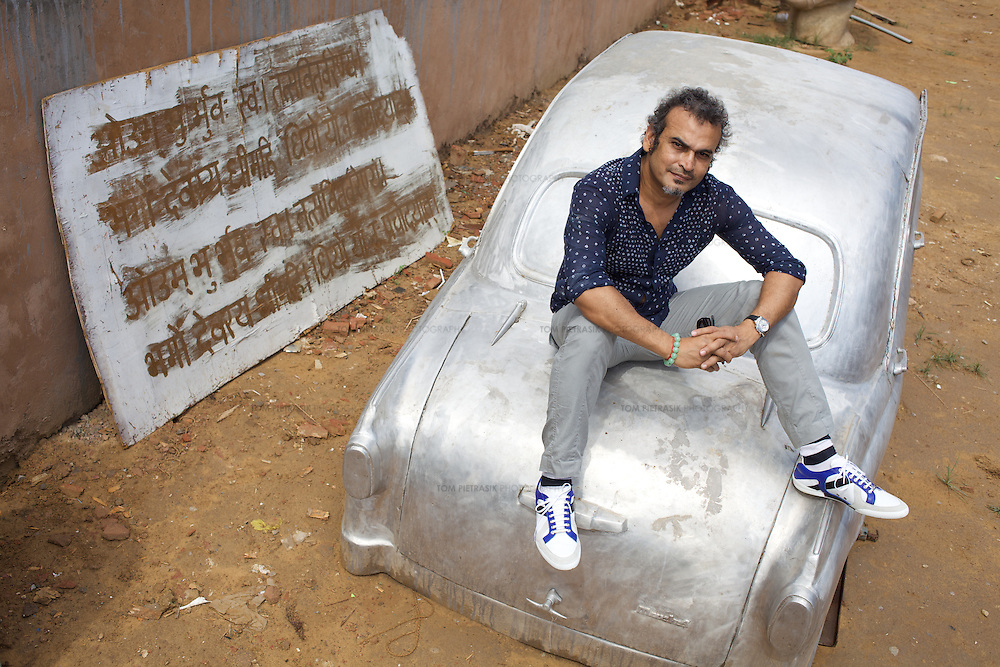 """Subodh Gupta, contemporary artist with one of his sculptures outside his recently completed studio in Gurgaon, a satellite town of Delhi...Gupta's most celebrated sculptures are constructed from common domestic items including the steel pots and pans that are a feature every Indian home. Of the kitchen-ware that forms the basis of his work, Gupta says,..""""The poor, the middle class and the rich use it at home. In this country, how many people have the utensils but they starve because there is no food?""""..Gupta was brought up, one of six children, to a railway-worker father in a north Indian village. ..Gupta's work fetches such huge sums of money. Two versions of his Mind Shut Down, modeled on the human skull and constructed entirely of steel kitchen utensils recently sold for EUR1 million each...Photo: Tom Pietrasik.Gurgaon, Haryana. India. .July 23rd 2009"""