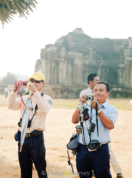 Local guides take many pictures of tour groups at the Angkor temple complex, Siem Reap Province, Cambodia