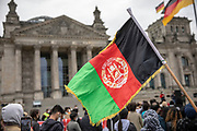 """A protester waves the Afghan national flag as people take part in a demonstration in front the Reichstag  building, seat of the German lower house of Parliament, the Bundestag in Berlin, Germany, August 17, 2021. About 1000 people gathered in front of the  under the call """"Airlift now! Create safe escape routes from Afghanistan!"""", the spontaneous event was organized by Seebrücke and several other human-rights organizations."""