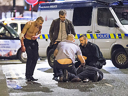 © Licensed to London News Pictures . 21/12/2013 . Manchester , UK . A man lies in the road and another looks on with a bleeding arm following a fight on the city's Charlotte Street . Christmas revellers out in the rain in Manchester on Mad Friday , the last Friday night before Christmas which is typically one of the busiest nights of the year for police and ambulance crews . Photo credit : Joel Goodman/LNP