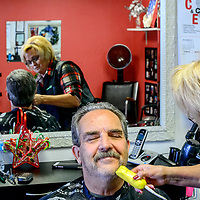 Grants mayor Modie Hicks bets a beard shave from Clorinda Brito at Clo's Hair Design in Grants Thursday. Hicks had his hair cut after a fundraiser to benefit the Marine ROTC drill team trip to a national competition.