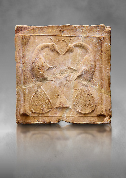 6th-7th Century Eastern Roman Byzantine  Christian Terracotta tiles depicting two Peacocks - Produced in Byzacena -  present day Tunisia. <br /> <br /> <br /> The patterns of peacock tails contain round decorations. These were seen to be the symbolic eyes of omnipotence and often ascribed to the Archangel Michael. The peacock's feather is sometimes associated with St. Barbara Also, The peacock, (due to an ancient myth that Peacock flesh did not decay), is seen as a symbol of immortality.<br /> <br /> These early Christian terracotta tiles were mass produced thanks to moulds. Their quadrangular, square or rectangular shape as well as the standardised sizes in use in the different regions were determined by their architectonic function and were designed to facilitate their assembly according to various combinations to decorate large flat surfaces of walls or ceilings. <br /> <br /> Byzacena stood out for its use of biblical and hagiographic themes and a richer variety of animals, birds and roses. Some deer and lions were obviously inspired from Zeugitana prototypes attesting to the pre-existence of this province's production with respect to that of Byzacena. The rules governing this art are similar to those that applied to late Roman and Christian art with, in the case of Byzacena, an obvious popular connotation. Its distinguishing features are flatness, a predilection for symmetrical compositions, frontal and lateral representations, the absence of tridimensional attitudes and the naivety of some details (large eyes, pointed chins). Mass production enabled this type of decoration to be widely used at little cost and it played a role as ideograms and for teaching catechism through pictures. Painting, now often faded, enhanced motifs in relief or enriched them with additional details to break their repetitive monotony.<br /> <br /> The Bardo National Museum Tunis, Tunisia. Against a grey art background.