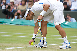 25.06.2011, Wimbledon, London, GBR, Wimbledon Tennis Championships, im Bild Rafael Nadal (ESP) picks up an insect during the Gentlemen's Singles 3rd Round match on day six of the Wimbledon Lawn Tennis Championships at the All England Lawn Tennis and Croquet Club, EXPA Pictures © 2011, PhotoCredit: EXPA/ Propaganda/ *** ATTENTION *** UK OUT!