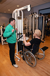 Instructor showing woman how to use weights at an inclusive fitness gym,