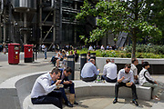 Lunchtime crowds eat takeaways in summer sunshine in Leadenhall in the City of London, the capitals financial district aka the Square Mile, on 10th July 2019, in London England.