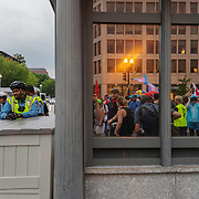 """Protesters are reflected in the glass of a White House security checkpoint on 17th street during the """"Unite the Right 2"""" rally in Washington, D.C. on Sunday, August 12, 2018."""