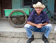 Old Cuban man sitting on a step wearing a stetson hat with a bike in the background, Palmira village in Cienfuegos province, Cuba