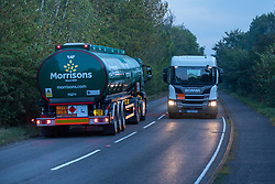 © Licensed to London News Pictures. 26/09/2021. Kingsbury, Warwickshire, UK. The scene as dawn breaks on a Sunday morning outside Kingsbury fuel depot, the main fuel distribution site in the Midlands. Pictured a Morrisons fuel tanker leaving the the Kingsbury site passes a returning ASDA fuel tanker. Photo credit: Dave Warren / LNP