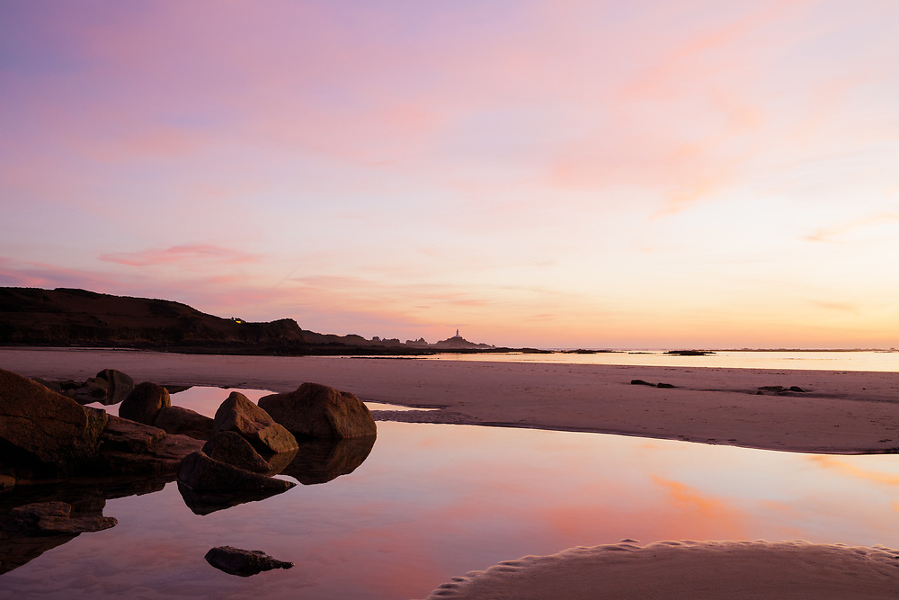 Pink and purple light reflecting in the glassy calm sea and water in the rock pools at St Ouen's Bay, Jersey, with Corbiere lighthouse in the distance