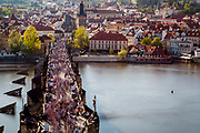 "Crowds are moving across Charles Bridge seen from The Old Town Bridge Tower which is one of the most beautiful Gothic gateways in the world. In the back Prague's ""Lesser Town"" (Mala Strana)."