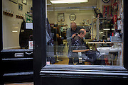 A gentleman has his neck clippered in a west end barber shop in central London.