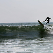 A surfer in action in a beach scene in the height of summer of Cisco Beach, Nantucket, Nantucket Island, Massachusetts, USA. Photo Tim Clayton