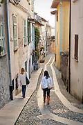 Two women walk down the streets of Orta San Giulio, Piedmont, Italy.