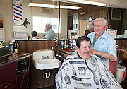Jerry Clayton, left, shares a laugh with barber Clyde Ashcroft during Clyde's last day cutting hair at his barbershop at 3609 S. State, Friday, Dec. 28, 2012. Clayton has been coming to get his hair cut from Ashcroft for over ten years.