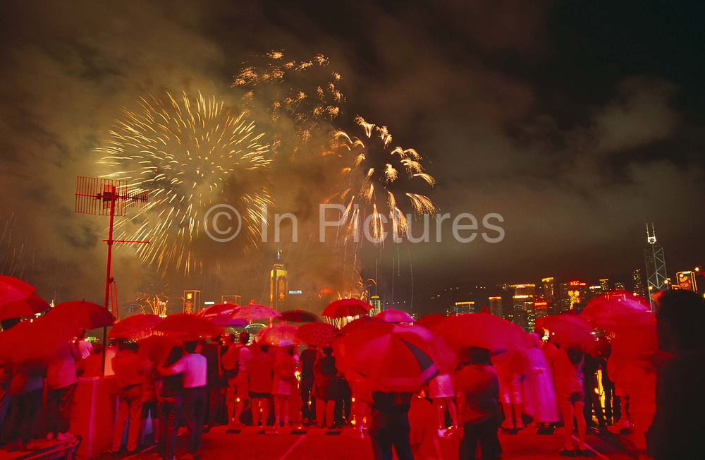 """In heavy monsoonal rain, crowds gather at the stroke of midnight beneath umbrellas to witness the transfer of sovereignty of Hong Kong from the United Kingdom to the Peoples Republic of China (PRC), often referred to as """"The Handover"""" on June 30, 1997. Midnight signified the end of British rule, and the transfer of legal and financial authority back to China. From the on the roof of Ocean Terminal shopping mall, the skyline is filled with fireworks but the glowing red comes from giant advertising lettering behind the viewer on the top floor of the building which protrudes out into Hong Kong harbour from the Kowloon side of the territory.  Hong Kong was once known as 'fragrant harbour' (or Heung Keung) because of the smell of transported sandal wood."""
