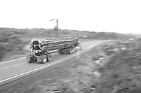 Log truck driving timber to mill through clear cuts in Oregon.