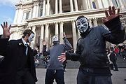 Masked demonstrators of Occupy London OSLX dance in front of St Pauls Catherdral, London.