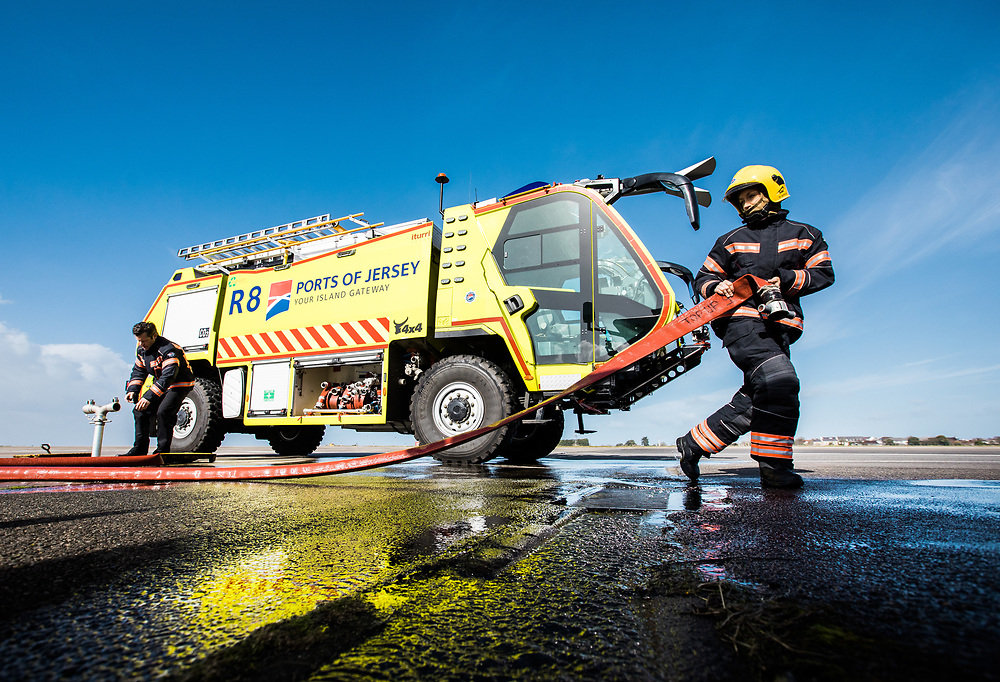 Fire engine parked on the runway at Jersey airport whilst the fire fighters work with the water hoses.