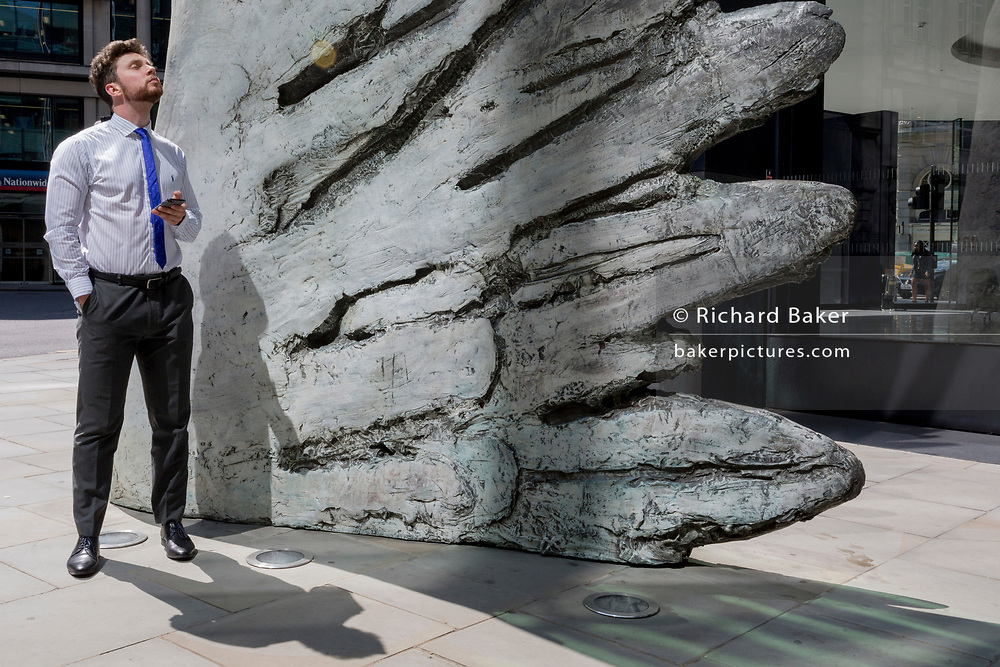 A financial industry businessman stands beneath the sculpture entitled City Wing on Threadneedle Street in the City of London, the capital's financial district (aka the Square Mile), on 11th July 2019, in London, England. City Wing is by the artist Christopher Le Brun. The ten-metre-tall bronze sculpture is by President of the Royal Academy of Arts, Christopher Le Brun, commissioned by Hammerson in 2009. It is called 'The City Wing' and has been cast by Morris Singer Art Founders, reputedly the oldest fine art foundry in the world.