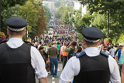 London, August 28th 2016. Police officers watch the thousands of revellers flooding Ladbroke Grove during Family Day at Europe's biggest street party, the Notting Hill Carnival.