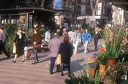 People walking in sunshine past flower stalls in Las Ramblas; Barcelona,