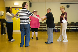 Woman Day Service Officer showing Day Service users with learning disability a line dancing class step,