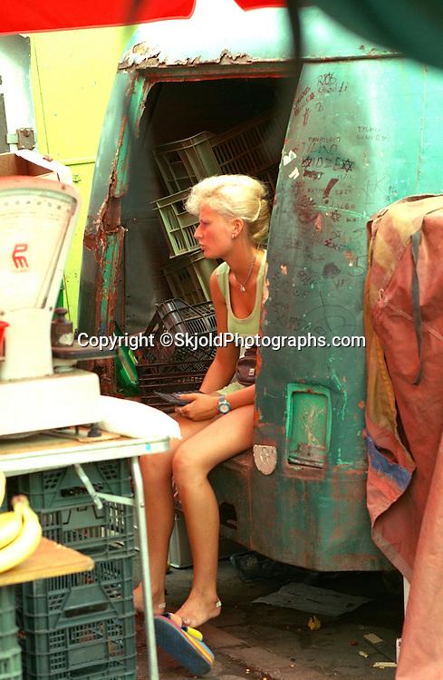 Woman vendor age 25 resting at flea market.    Lodz Poland