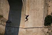 """Adem Mocca Pajevic jumps from the Old Bridge...Divers and tourists at Mostar's famous Old Bridge (Stari Most) in Bosnia and Herzegovina. This bridge is the city and region's biggest tourist attraction and there are busses full of tourists coming in from Sarajevo and Dubrovnik, Croatia. For 25euros tourists can train to jump from the bridge themselves, under supervision from the """"professional"""" Mostar divers known as the Mostari. .."""