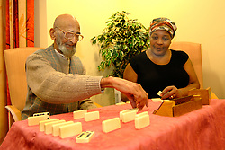 An elderly sikh man plays dominoes with a Care Assistant in a  multi-cultural elderly people's  Day Centre; Bradford; Yorkshire