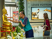 "10 APRIL 2014 - BANGKOK, THAILAND:  Thais line up at Siam Paragon, an upscale mall in Bangkok, to bathe a Buddha statue put out for Songkran. Songkran, also called the ""Water Festival"" is the traditional Thai New Year. It was celebrated as the New Year until 1940, when Thailand made January 1 the official start of the New Year. Songkran is now a three day holiday starting on April 13. Many people go to temples to make merit in the days leading up to Songkran. They bathe Buddha statues to bring themselves good luck in the coming year. The holiday is best known for water fights and throwing water at strangers. Thais and foreigners go out with giant squirt guns or buckets of water and throw the water at strangers.   PHOTO BY JACK KURTZ"