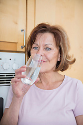 Portrait of senior woman in kitchen with water glass, smiling