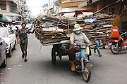 Recycling workers load up a motorbike and trailer with cardboard for recycling, Phnom Penh. Rural peasants who have left the countryside in search of earning a decent living often end up as recycling workers on Phnom Penh's city streets. They earn a few dollars a day from selling by weight the plastic bottles, aluminium cans and cardboard they collect during a days work. Usually they work from the mid afternoon until midnight, sorting through the rubbish on the streets. They take what they collect to small sorting houses on the edge of the city.