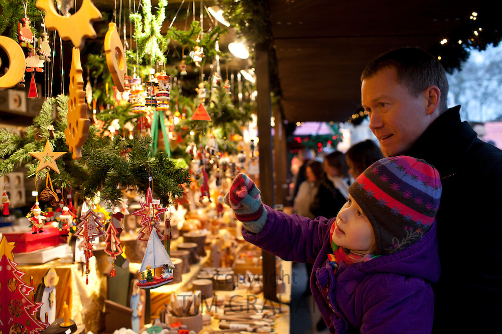 Father and child shopping for Christmas ornaments at Christmas market, Winter Wonderland, in Hyde Park, London