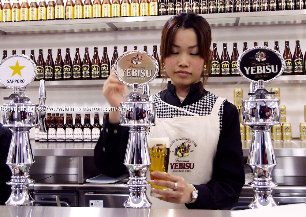 Female bartender pouring beer at Sapporo brewery in Hokkaido Japan