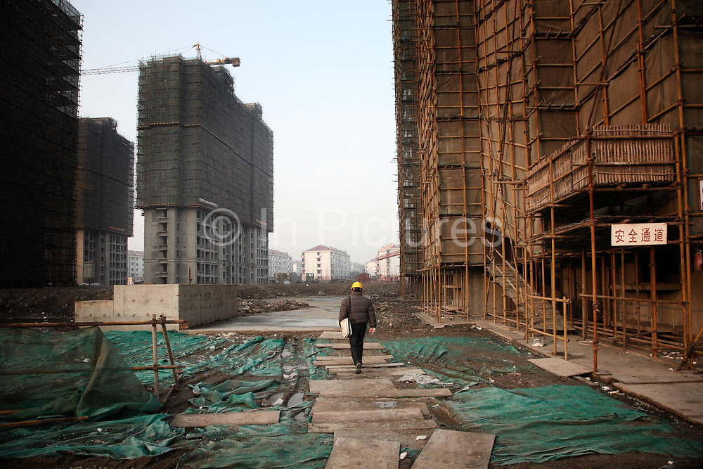 """A worker walks through the grounds of an unfinished apartment  complex in Shanghai, China on 29 December, 2009.  China has tightened land-sale regulations for developers in its latest attempt to take some of the steam out of the potentially overheating property market, this followed a recent vow from Beijing last week to curb what it calls an """"overly fast"""" rise in property prices by boosting the supply of cheap public housing and redeveloping slum areas.."""