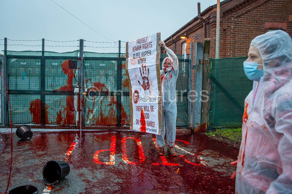Activists take radical action throwing buckets of fake blood at Napier Barracks to highlight human rights violations on the 28th of January 2021 in Folkestone, United Kingdom. Activists dressed in white suits and masks, threw the fake blood through the gates of Napier Barracks to send a clear message to Priti Patel and the Home office to close Napier camp or there will be blood on your hands Following ongoing concerns over the poor living conditions at Napier barracks, and the failures in handling the inevitable Covid-19 outbreak onsite, pressure has been mounting on the Home Office to close the camp.