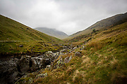 The valley with Ulls water river running through it looking up through the rain and clouds at Helvellyn, The Lake District, United Kingdom.