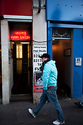 Man walks past a unisex hair salon / hair studio sign. The neon sign in a doorway looks slightly seedy but is entrance to a reputable hair salon.