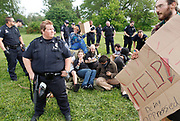 Occupy protesters sit on a tent after it was torn down by police in a grassy area near the B-Line Trail. (Photo by Jeremy Hogan)