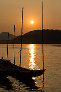 Traditional boats docked to bamboo poles in the Mekong River at sunset, Luang Prabang, Laos.