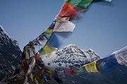 Colorful Buddhist prayer flags, flapping in the wind at Annapurna Base Camp, frame the towering peak of Annapurna South (7219m), Annapurna Sanctuary, Himalaya Mountains, Nepal.