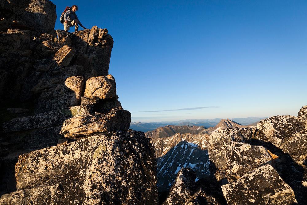 Kevin Steffa scrambles down the steep summit block of Golden Horn at sunset in Okanogan National Forest, Washington.