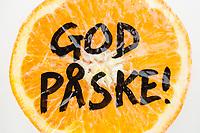 Påskehilsenen «God påske!» skrevet over fruktkjøttet på en delt appelsin som ligger i snøen.