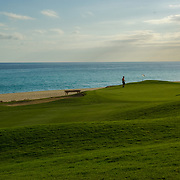 Couple playind golf at Cabo Real Golf Course. Los Cabos, Mexico.