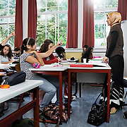 Nederland Rotterdam 23-09-2009 20090923 Serie over onderwijs,   openbare scholengemeenschap mavo, havo en vwo. Lesuur in klaslokaal, lerares geeft klassikaal  toelichting op de lesstof en stelt de leerlingen vragen.  , students, studeren, studie, studieboek, studies, studieuur, study, studying, teacher, teaching, the netherlands, the netherlands vaardigheden, toekomst, toelichten, toelichting geven, uitleg, uitleg geven, uitleggen, vaardigheden, vaardigheid, vinger in de lucht houden, vinger in de lucht steken, vinger opsteken, voor de klas staan, voortgezet, vrouw, young, zelfstandig werken, zich informeren                                             .Foto: David Rozing