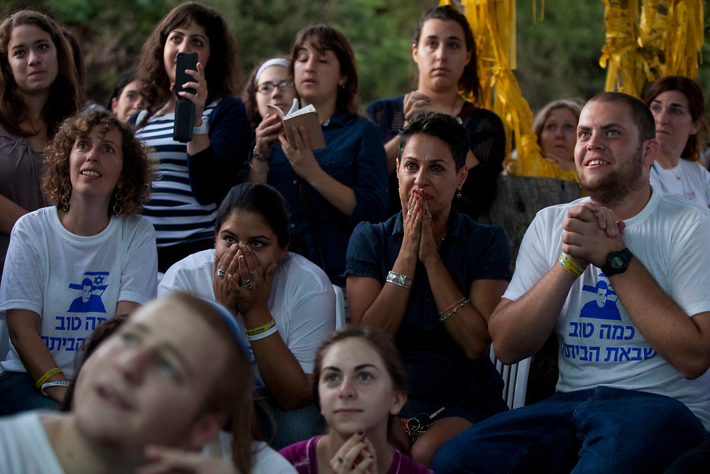Israelis react as they watch a live broadcast on television showing Israeli Defense Forces soldier Gilad Shalit as he arrives at his home town of Mitzpe Hila, Israel, on October 18, 2011, outside a protest tent set to call for his release, near Prime Minister Netanyahu's residence in Jerusalem. Shalit was freed after being held captive for five years in Gaza by Hamas militants, in a deal which saw Israel releasing more than 1,000 Palestinian prisoners.