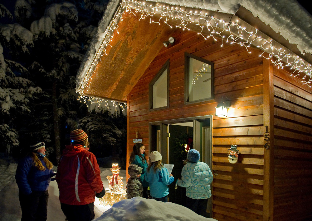 Alaska, Girdwood.  A group of people sing Chrristmas carols for their neighbors during a snowy winter night. Festive holiday lights decorate the log cabin.